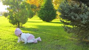 Infant crawling around in park. An infant girl in white and pink suit crawls on green lawn in a pictorial city park with trees and smiles on sunny day in autumn stock footage
