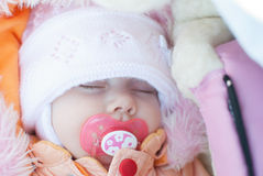 Infant girl sleep. Infant girl on a winter walk in a carriage Stock Photos