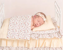 Infant in hairband napping under the sheets Royalty Free Stock Photo