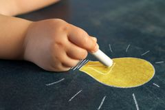 Infant hand drawing a light bulb. Stock Image