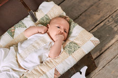 Infant with hand in mouth. Small kid lying on blanket. Baby hunger signs Stock Photos