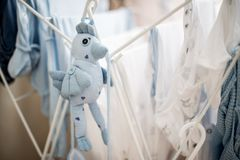 Soft toy blue bird near infant baby laundry drying Stock Images