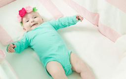 Infant lies on her back in a baby crib. Baby is dressed in a suit for babies Stock Photo