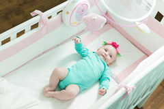 Infant lies on her back in a baby crib. Baby is dressed in a suit for babies Royalty Free Stock Images