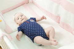 Infant lies on her back in a baby crib. Baby is dressed in a suit for babies Royalty Free Stock Photo