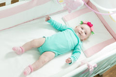 Infant lies on her back in a baby crib. Baby is dressed in a suit for babies Stock Photos