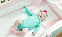 Infant lies on her back in a baby crib. Baby is dressed in a suit for babies Stock Photography