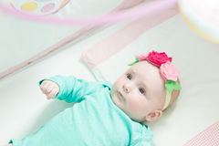 Infant lies on her back in a baby crib. Stock Images