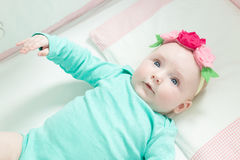 Infant lies on her back in a baby crib. Royalty Free Stock Images