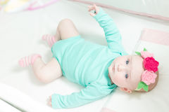 Infant lies on her back in a baby crib. Royalty Free Stock Photo