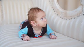 Infant lies on the sofa. Cute happy Infant lies on the sofa stock footage