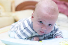 Infant lying and looking. Trying to lift up the head Royalty Free Stock Photography