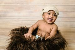 Infant mixed race healthy looking baby boy wearing knitted hat sitting in a fluffy furry basket wooden background modern studio sh. Oot vintage look smiling Royalty Free Stock Photos