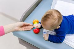 Infant with mother playing on changing table. Mom giving rattle toy to baby boy. View from above stock image