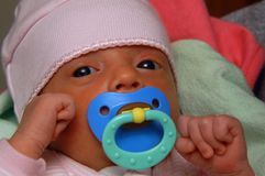 Infant with Pacifier. An infant with a pacifier in her mouth Stock Photo
