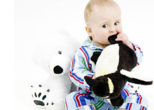 Infant in pajamas with stuffed animals stock images