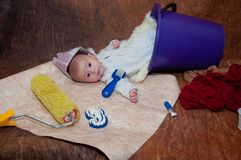 Repairing. Little child in hat mae of newspaper, laying in bucket near different instruments, wallpaper royalty free stock photo