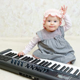 Infant with piano Stock Image