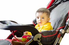 Infant playing on black & red stroller Royalty Free Stock Photo