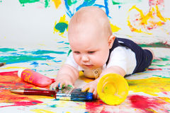 Infant  playing with paintbrush. A curious infant lying on the floor and playing with paintbrush Royalty Free Stock Photos