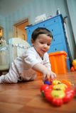 Infant plays on floor, soft focus Stock Photo
