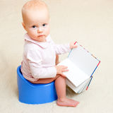 Infant on potty. Little baby girl sitting on blue potty with open book royalty free stock images