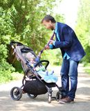 Infant in a pram holds his father by the tie. Businessman and his son in a pram, infant holds his father by the tie Royalty Free Stock Photography