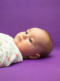 Infant on a purple background. Royalty Free Stock Photo