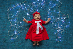 Infant in red dress lies and smiles on a blue background with Christmas lights Stock Photos