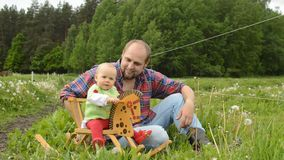 Infant rocking horse. Father ridding infant girl on baby horse toy in meadow stock video footage