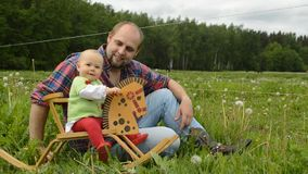 Infant rocking horse. Father ridding infant girl on baby horse toy in meadow stock video