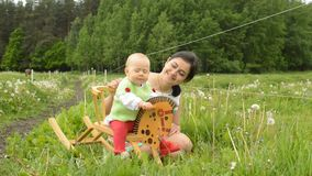 Infant rocking horse. Mother ridding infant girl on baby horse toy in meadow