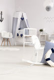 Infant room in coastal style. Beautiful white baby room with crib and rocking horse with decorations in navy style Royalty Free Stock Photos