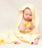 Infant with rubber duck. Eight month baby girl playing with rubber duck royalty free stock photography