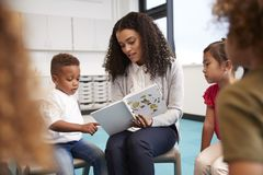 Infant school boy pointing in a book held by the female teacher, sitting with kids in a circle on chairs in the classroom, close u stock photo
