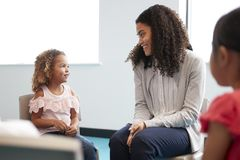 Infant school girl and her female teacher sitting on chairs in a classroom smiling to each other, close up stock photo