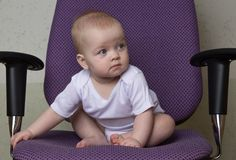 The infant is sitting on the office chair stock photography