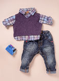Infant size shirt, sweater and jeans with toy Stock Photos