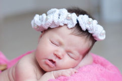 Infant sleeping in basket with accessory - head band, baby girl lying on pink blanket, cute child newborn. Infant sleeping in basket with accessory - head band Royalty Free Stock Images