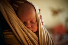 Infant sleeping in a sling. One month old baby sleeping in a sling Royalty Free Stock Photos