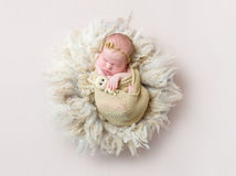 Infant sleeping swaddled with rabbit toy, topview. Adorable infant girl sleeping swaddled with her tiny brown toy of a rabbit, topview Stock Photography