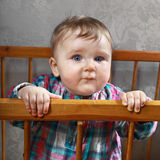 Infant. Stands in crib and looks Royalty Free Stock Images
