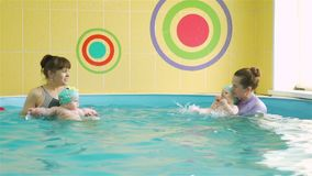 Infant swimming class with instructors in a pool. Infant swimming class with instructors in a paddling pool in slow motion. Little babies swimming and doing stock footage