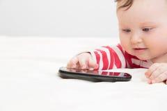 Infant touching smart phone Stock Photo