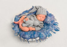 Infant with toy on a fluffy pillow Stock Images