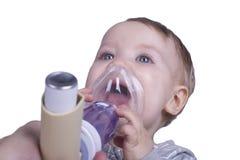 Infant using asthma inhalator Stock Photo