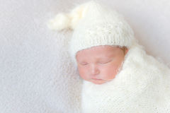 Infant wearing a warm white hat sleeping, closeup Stock Images