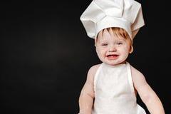 Infante adorável no chapéu do cozinheiro e do avental Imagens de Stock Royalty Free