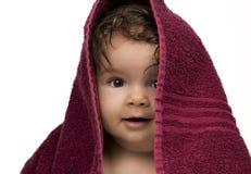 Infante che guarda fuori da sotto l'asciugamano rosso fotografia stock libera da diritti