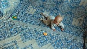 Infante che si trova sul letto, giocante con i giocattoli nel timelapse stock footage